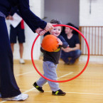 Boy throwing ball through hoop.