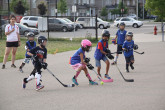 Children playing ball hockey outdoors.