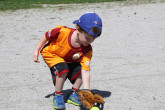 Young boy picking up tennis ball with baseball glove.