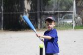 Young boy hitting tennis ball off a ball-holder with a baseball bat.