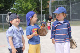 Children laughing together while playing outdoor baseball.