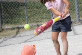 Young girl hitting tennis ball off a cone with a baseball bat.