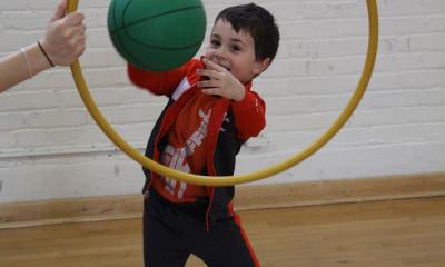 Child throwing basketball through hoop.