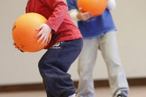 Two happy boys holding volleyballs during Sportball multi-sport class.