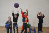 Happy kids throwing balls in the air during Sportball multi-sport class.