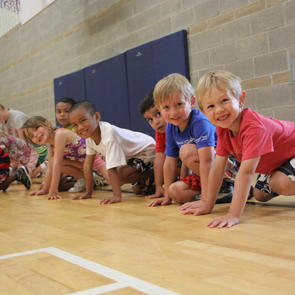 Smiling children ready to race during Sportball multi-sport class.