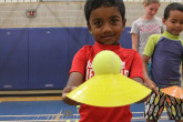 Young boy holding tennis ball and cone during Sportball multi-sport class.