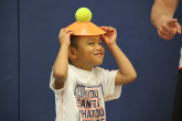 Young boy balancing ball and cone on head during Sportball multi-sport class.
