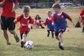 Young boys running on field during Sportball soccer class.