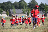 Toddlers running behind Sportball coach on soccer field.