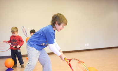 Boy lining up ball to hit with tennis racquet.