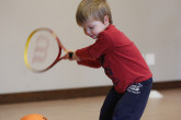 Boy swinging to hit ball with tennis racquet.