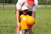 Sportball coach showing boy how to hold volleyball.
